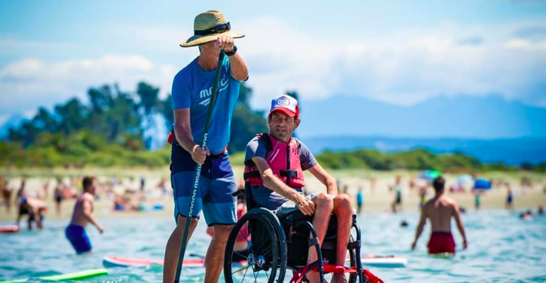 A man in a wheelchair by the beachside with another man helping him navigate the water with his oars.